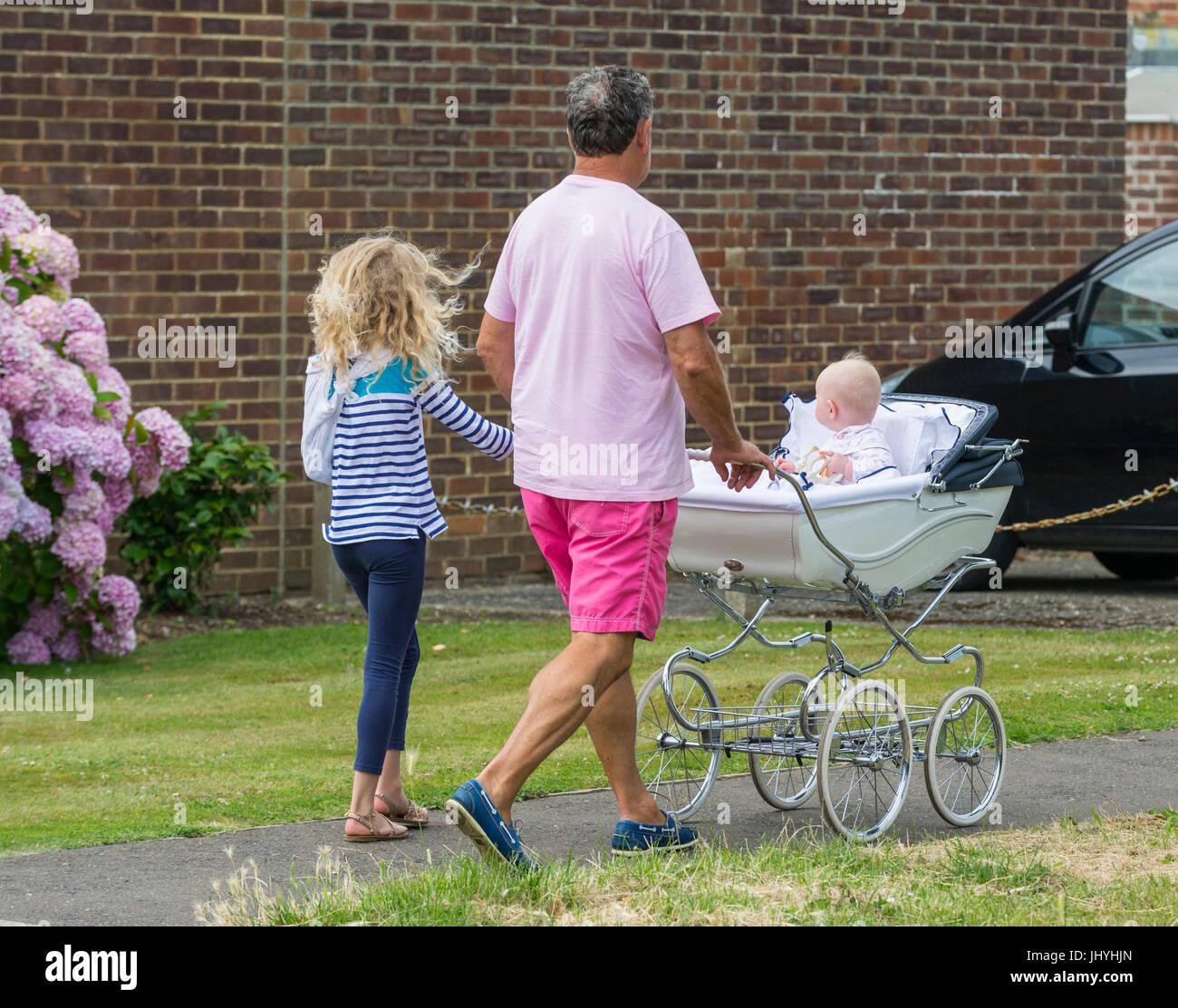 Hombre caminando con un niño y empujando un cochecito con un bebé. Familias monoparentales. Imagen De Stock