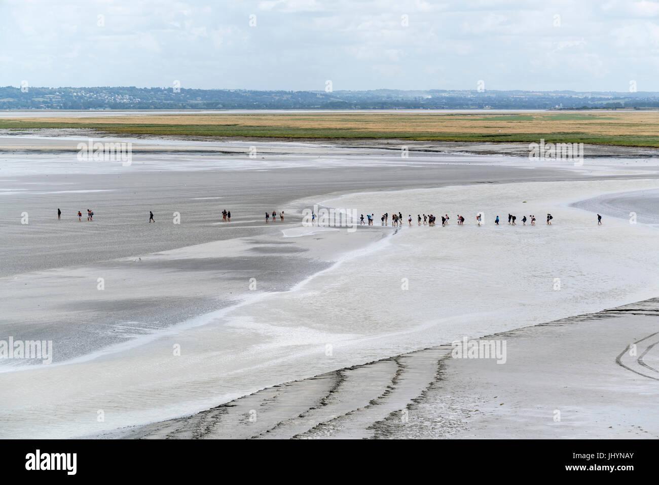 La gente caminando en la arena durante la marea baja, el Mont-Saint-Michel, en Normandía, Francia, Europa Foto de stock