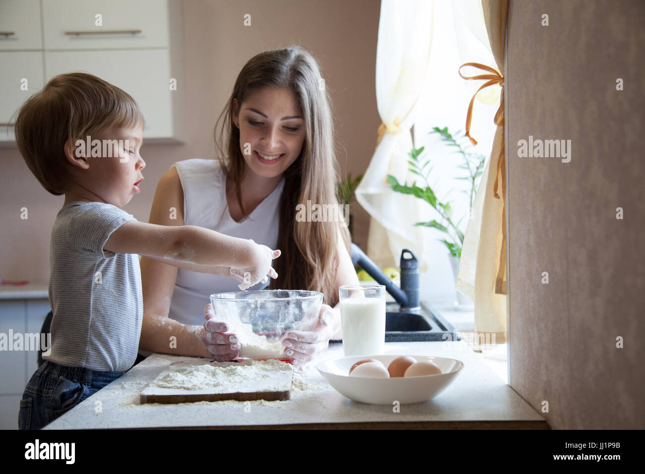 Madre e hijo preparar tarta con harina Foto de stock