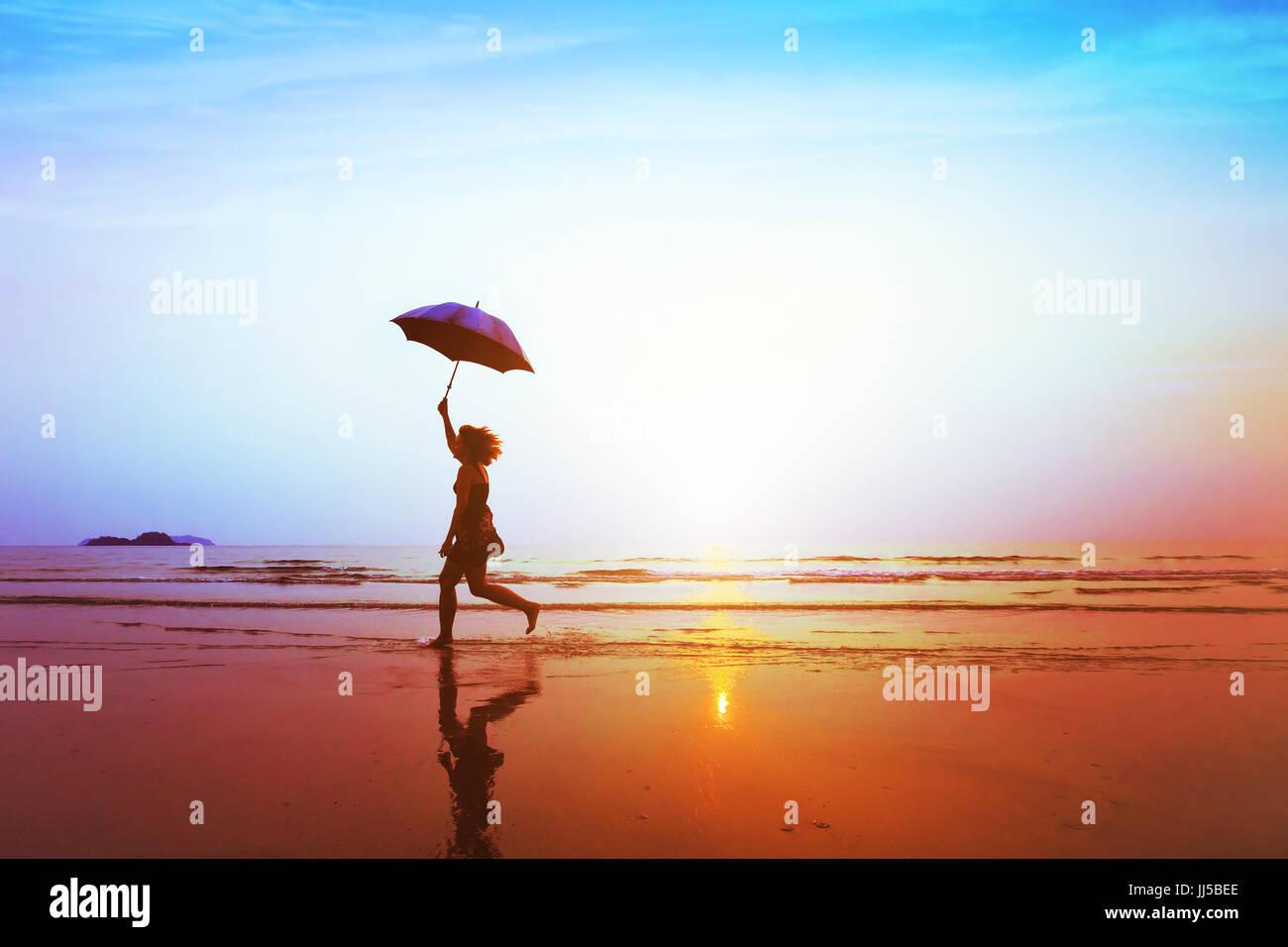 Silueta de niña despreocupada, feliz saltando con sombrilla en la playa al atardecer, libertad y alegría, Imagen De Stock