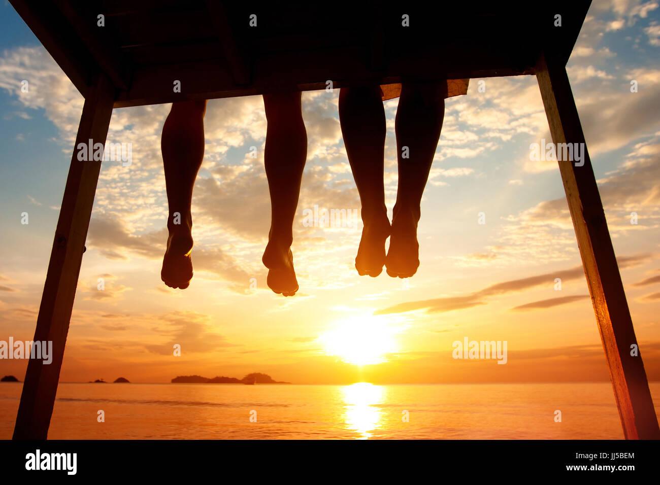 El concepto de la felicidad, la silueta de los pies de la pareja sentada en el muelle en sunset beach Imagen De Stock