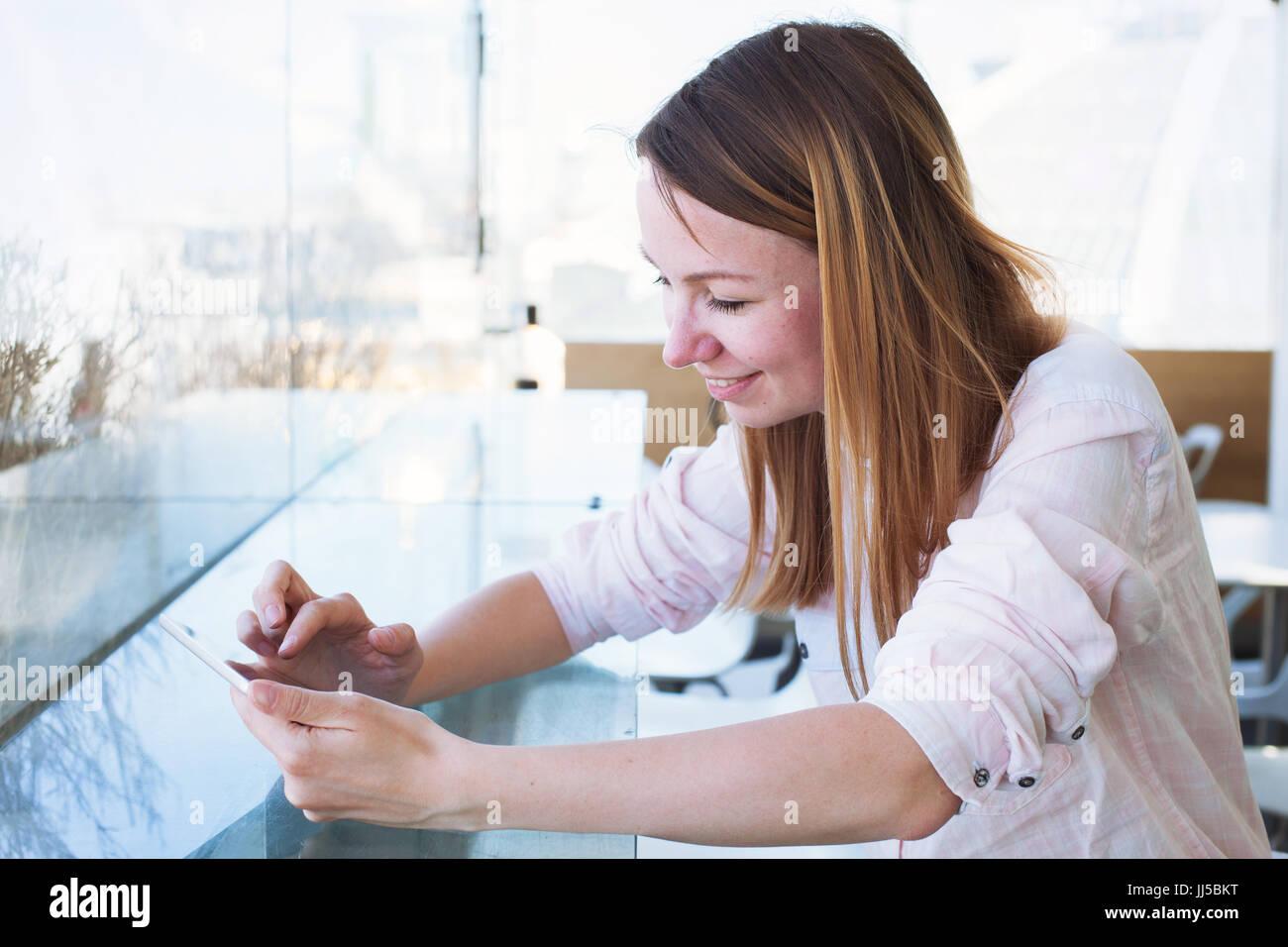Sonriente mujer caucásica leer correos electrónicos en línea en digital tablet pc, joven con acceso Imagen De Stock