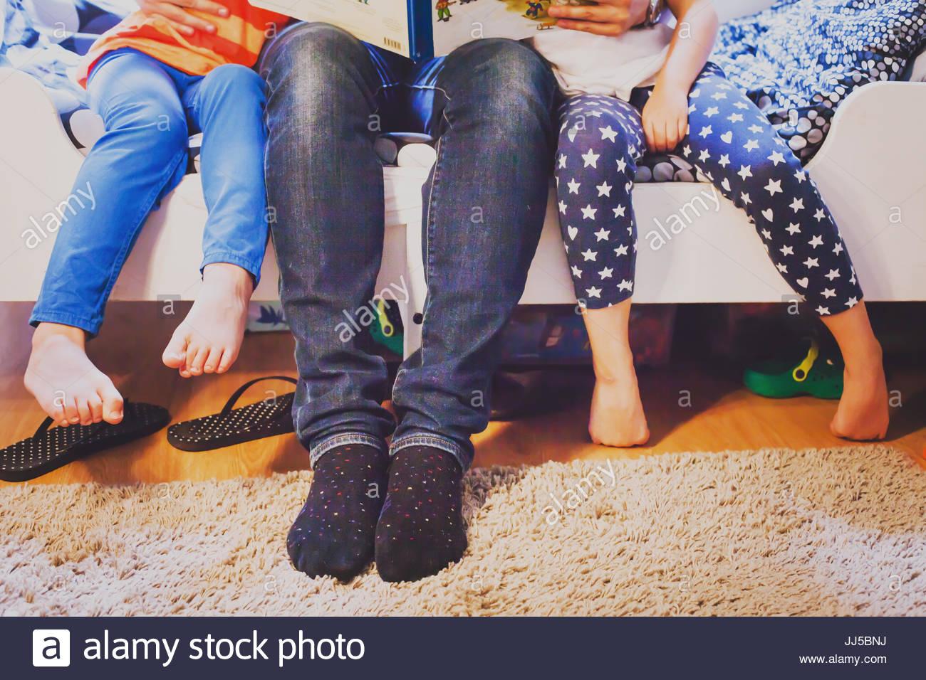 Padre en casa con dos niños sentados juntos y libro de lectura, las piernas de la familia Imagen De Stock