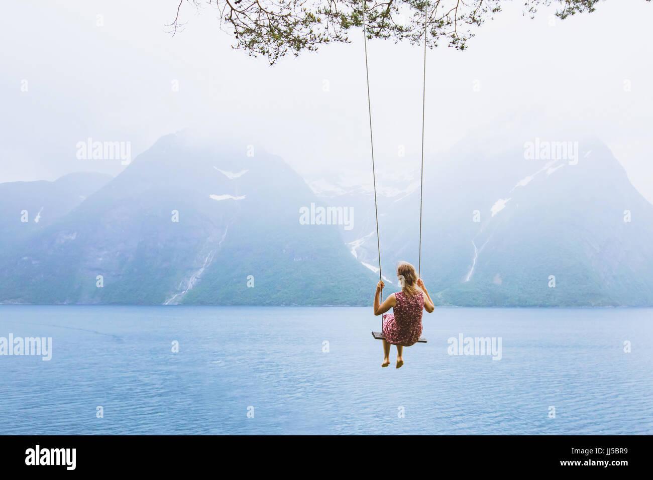 Hermosa chica romántica sobre columpio en Noruega, feliz soñador, inspiración antecedentes Imagen De Stock