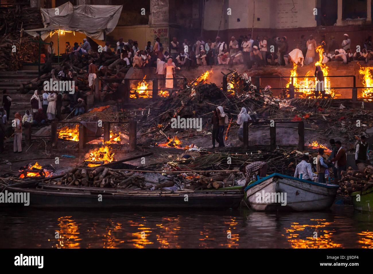 La cremación piras funerarias temprano en la noche. Manikarnika Ghat, Varanasi, Uttar Pradesh, India. Imagen De Stock