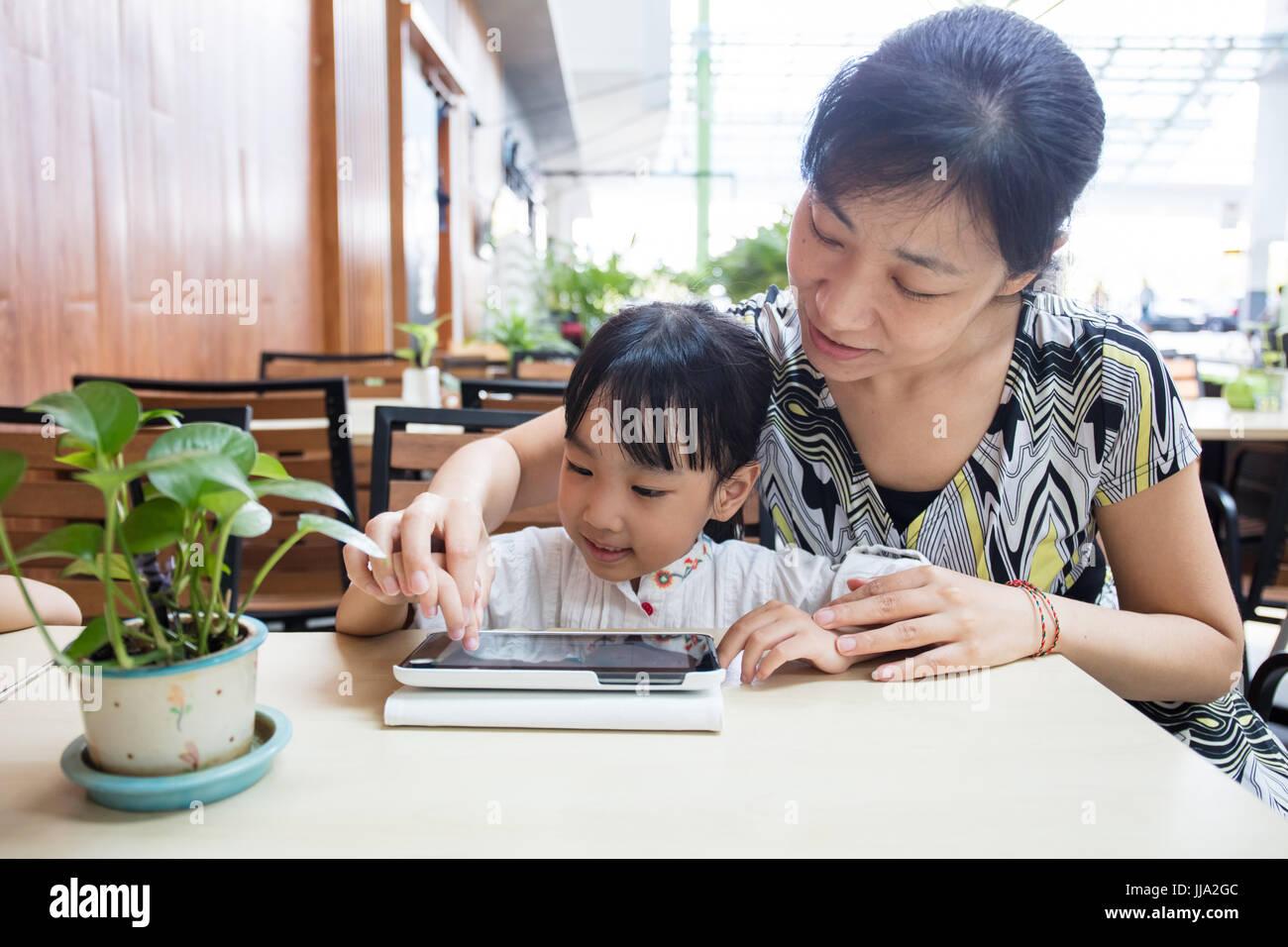 Chino Asia niña jugando tablet pc con su madre en la cafetería al aire libre Imagen De Stock
