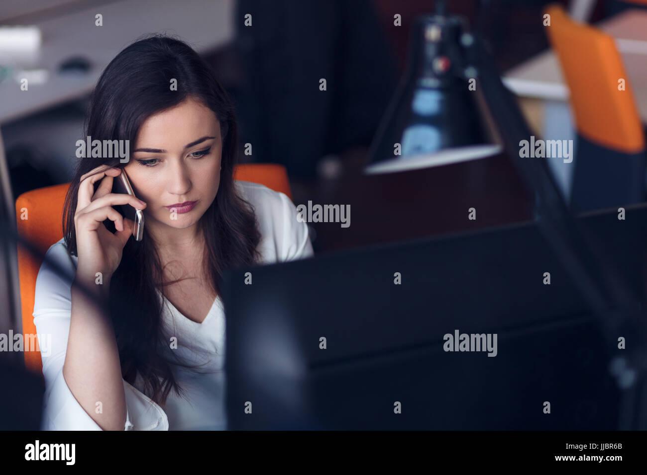 Hermosa joven trabajando en equipo y hablar por teléfono Imagen De Stock