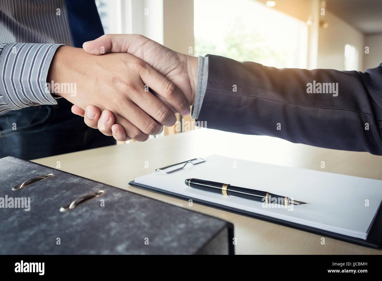 Parte media de un empresario de un apretón de manos con un entrevistador femenina recortada en la oficina. Imagen De Stock