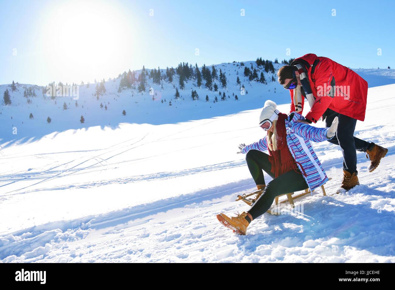 Pareja joven el trineo y disfrutando en los soleados días de invierno Imagen De Stock