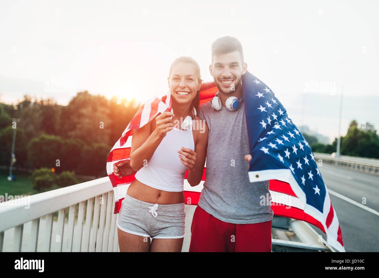 Retrato de fitness atractivo par la celebración de bandera americana Imagen De Stock