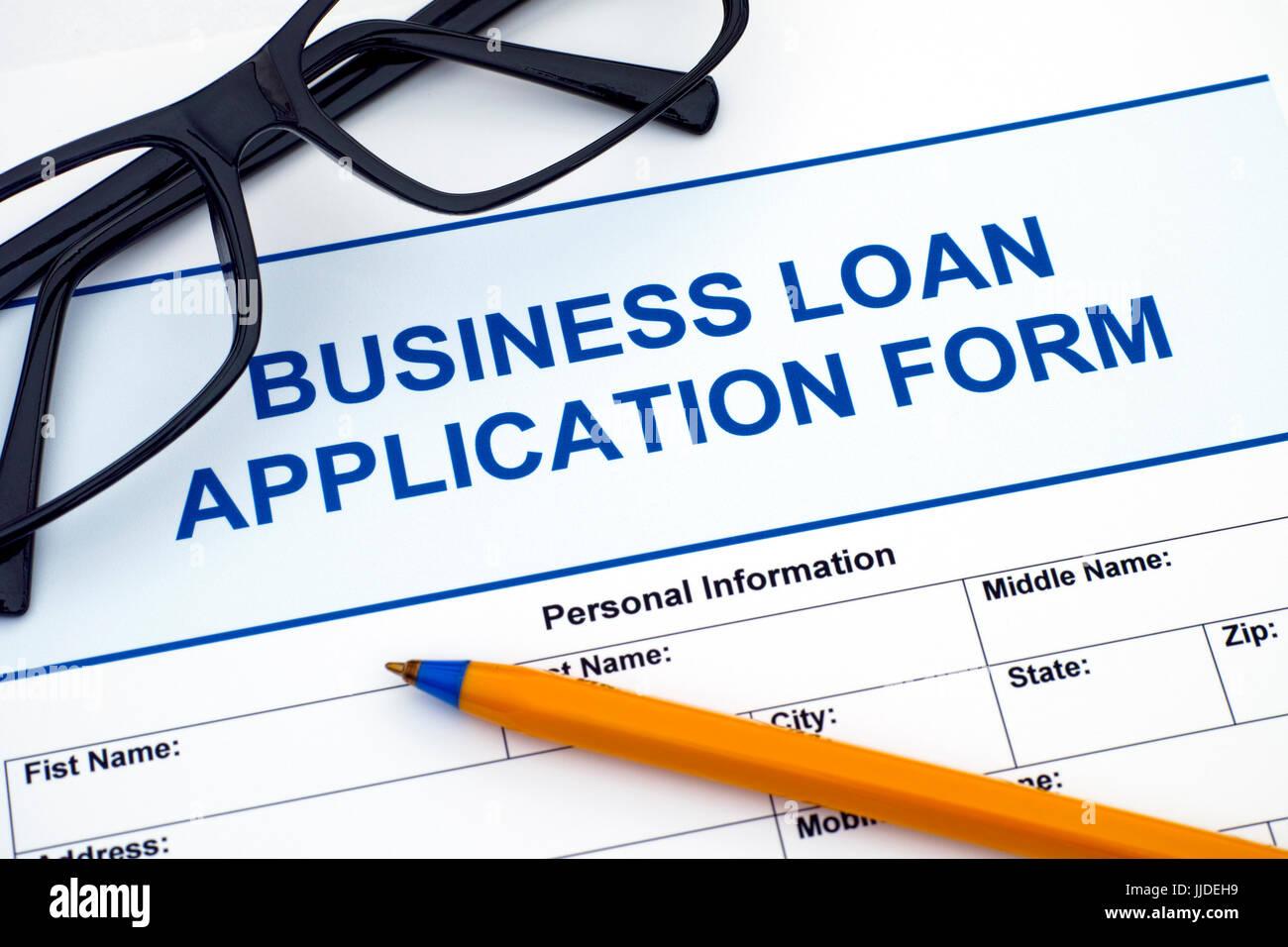 Formulario de solicitud de préstamos comerciales con bolígrafo y gafas. Imagen De Stock