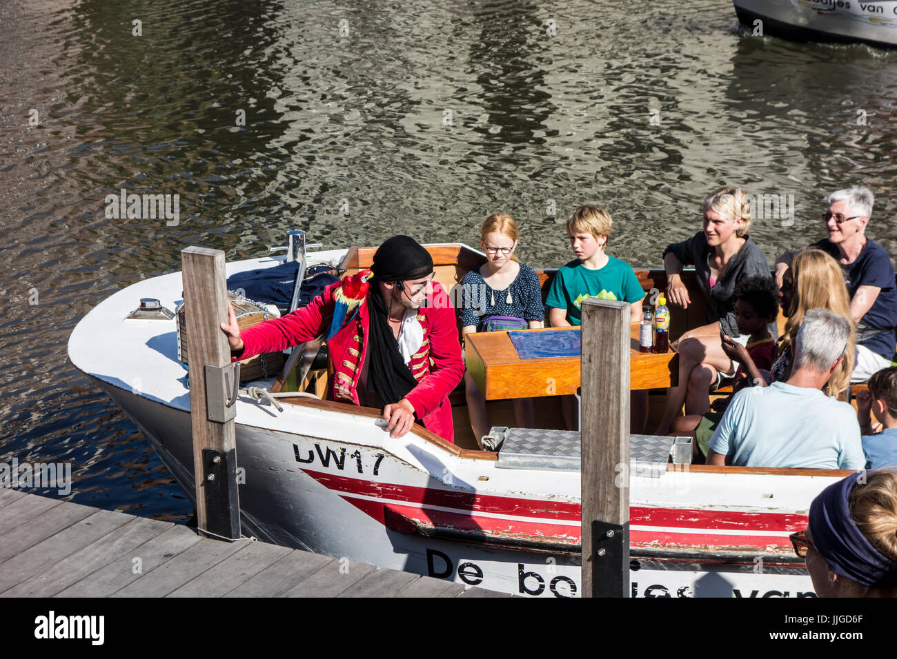 Guía de la ciudad vestidos como pirata en barco sobre el río Leie / Lys guiando turistas en viaje de turismo Imagen De Stock