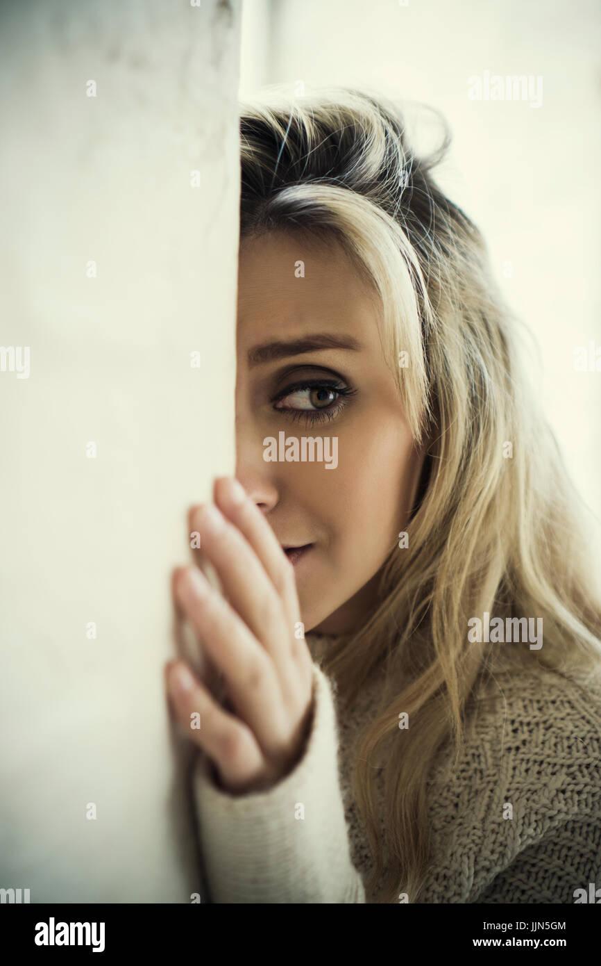 Asustada joven escondido detrás de la pared mirando lejos de llorar Imagen De Stock