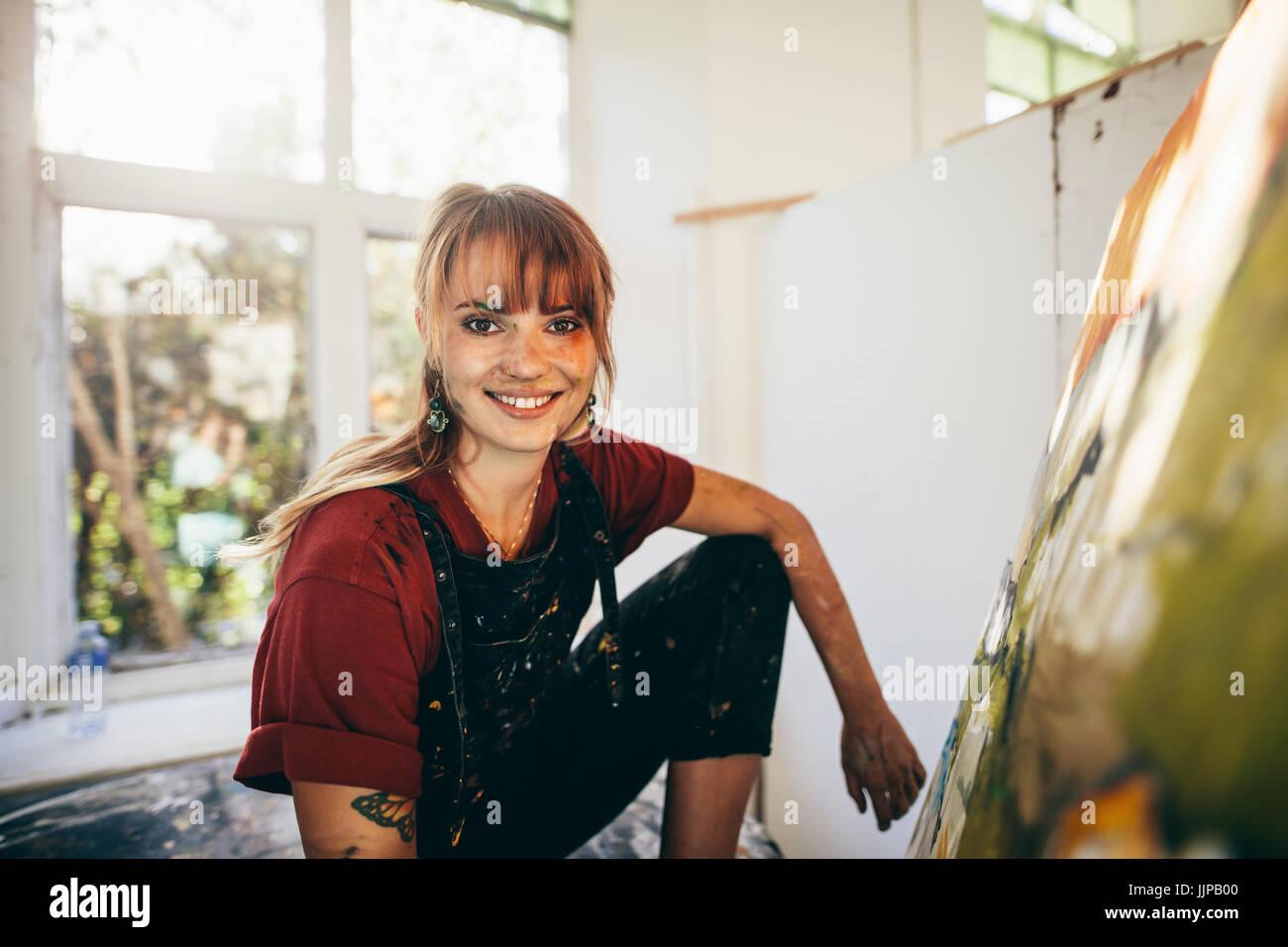 Interiores de filmación profesional pintor femenino en el estudio. Mujer artista haciendo una pintura sobre lienzo Foto de stock