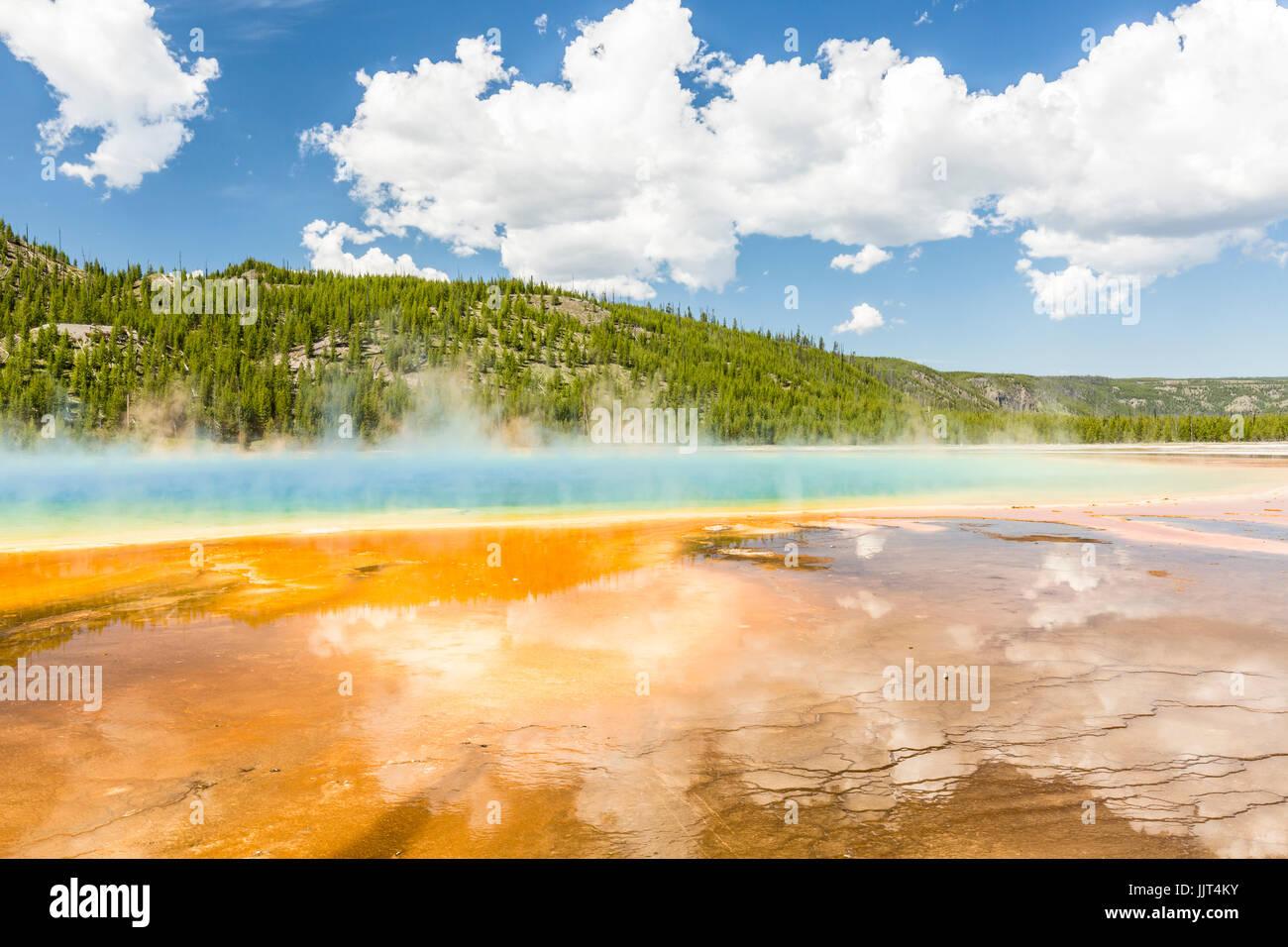 Las nubes reflejan en los vívidos colores del arco iris de la Grand Prismatic Spring, en el Parque Nacional Yellowstone, Wyoming Foto de stock