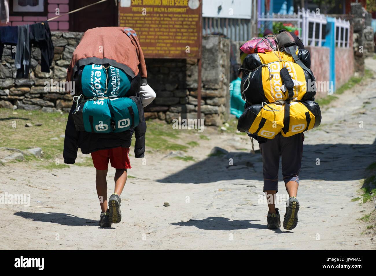 Cargadores cargando trekker para las bolsas en el circuito de Annapurna. Imagen De Stock