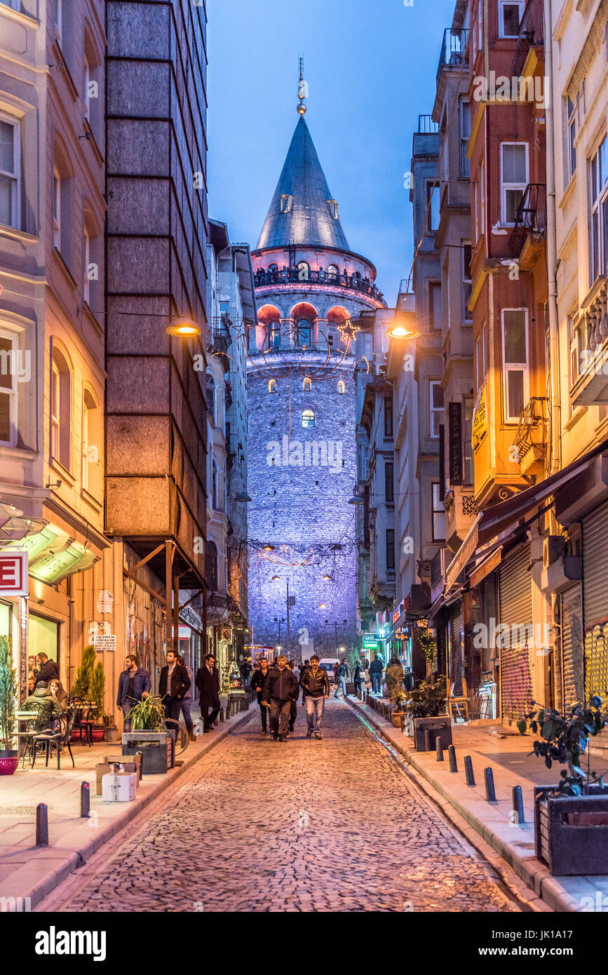 Vista nocturna de la vieja calle estrecha con la torre de Galata(Turco: Galata Kulesi)llamado Cristo Torre por genovés, Imagen De Stock