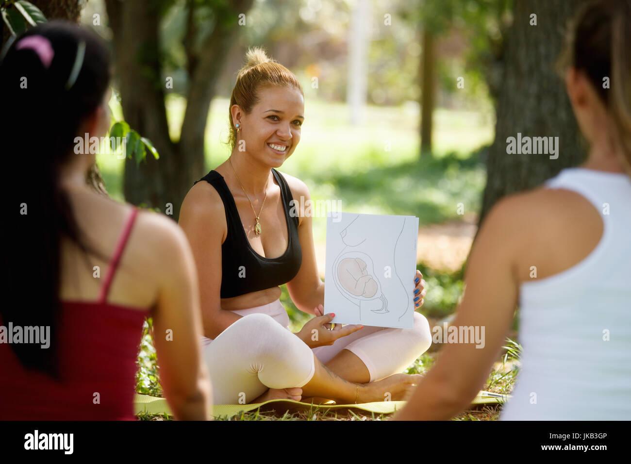 Mujeres embarazadas que tomaban lección prenatal en el parque. Profesor explicando el crecimiento del bebé dentro Foto de stock