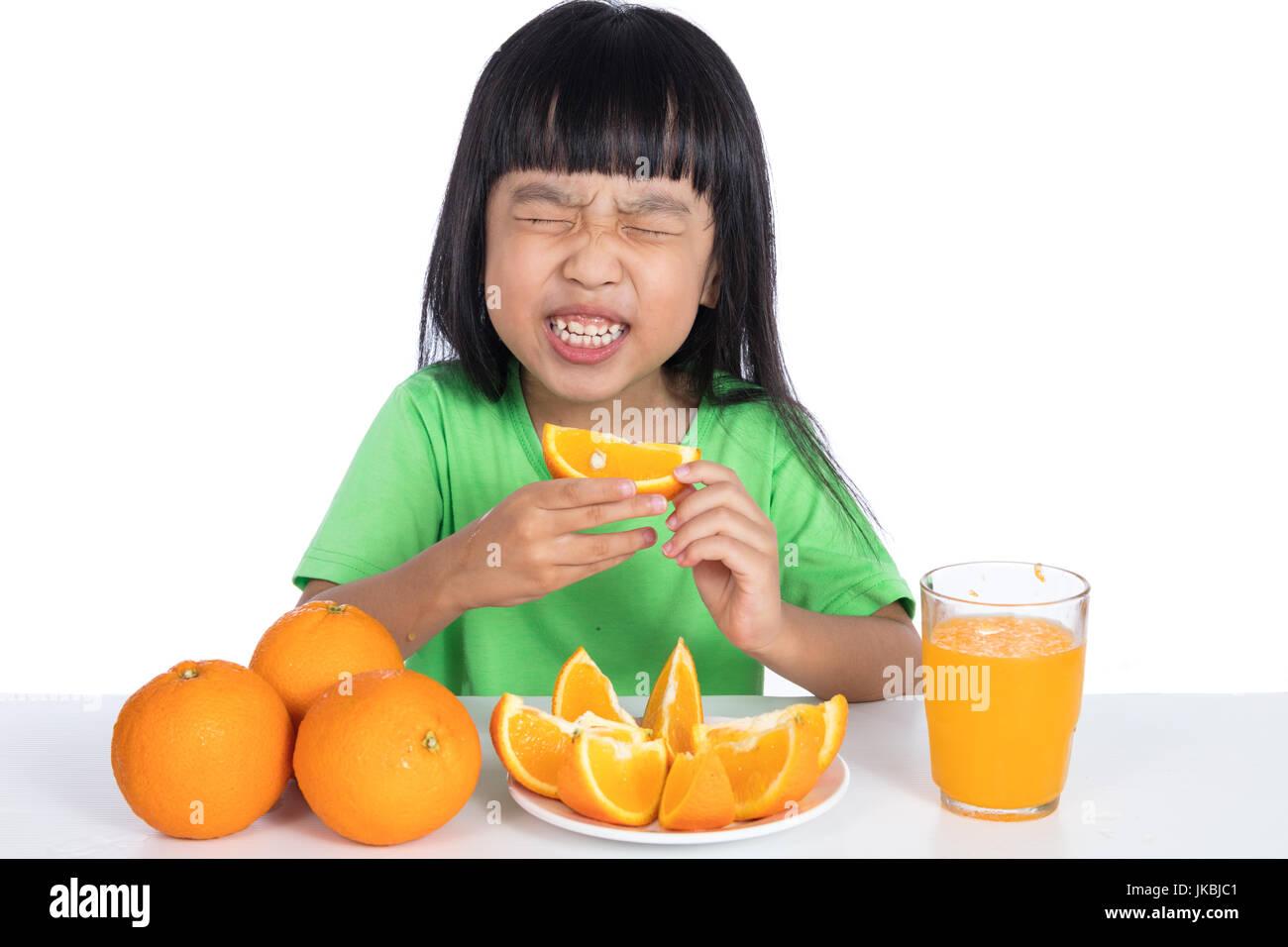 Chino Asia niña comer naranja agria y haciendo mueca aisladas en fondo blanco. Imagen De Stock