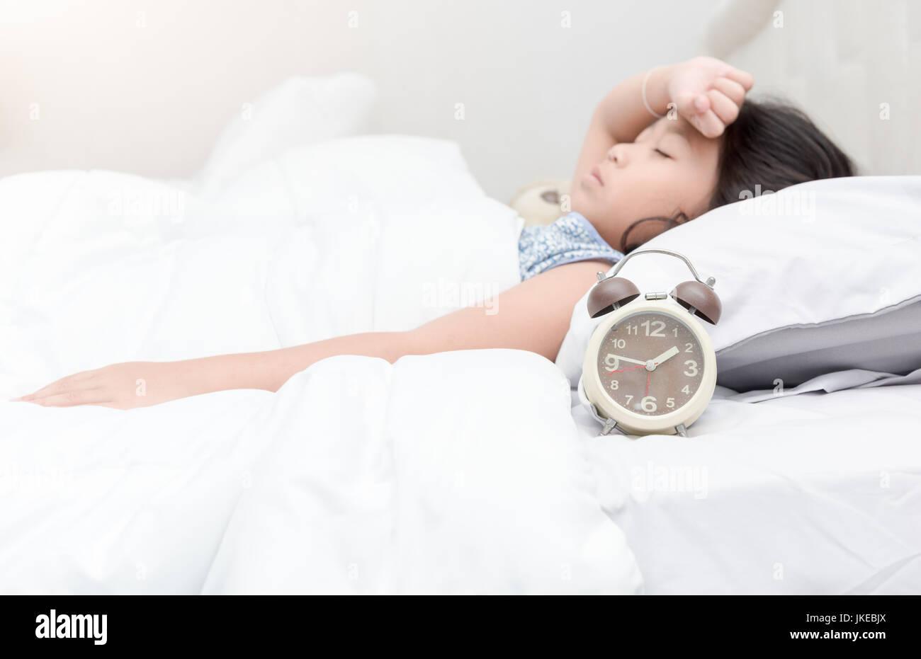 Alarma en la cama con el niño enfermo acostado padeciendo un dolor de cabeza Imagen De Stock