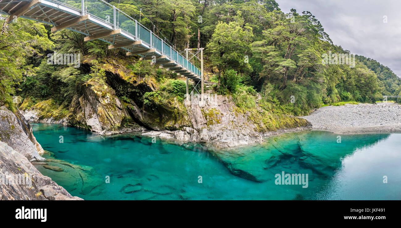 Nueva Zelanda, Isla del Sur, Parque Nacional Monte aspirantes, azul piscinas en río makarora con puente colgante. Imagen De Stock