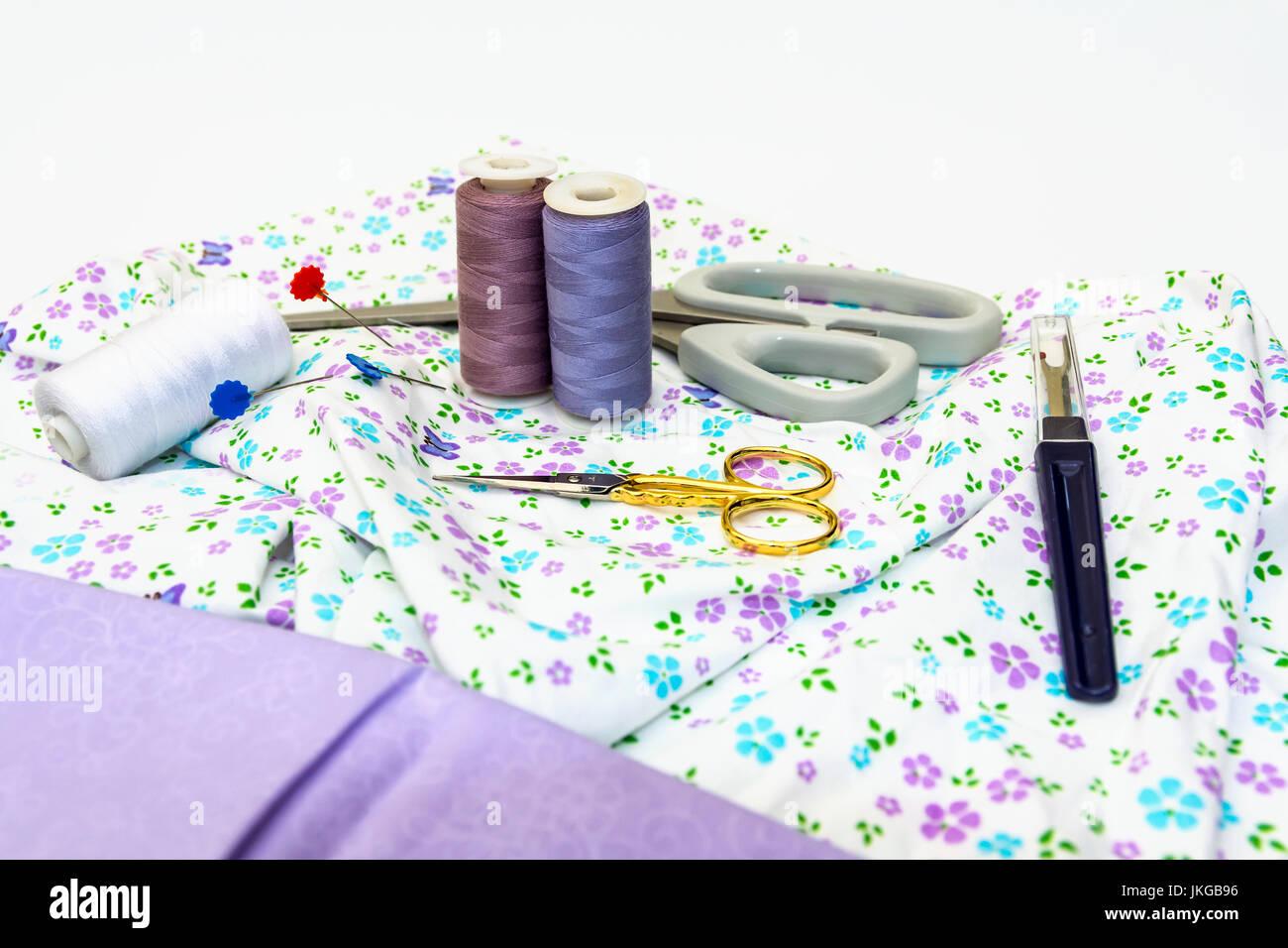 Una selección de accesorios de costura, como tijeras, algodón, con tejido normal y patrón aparece sobre fondo blanco. Foto de stock
