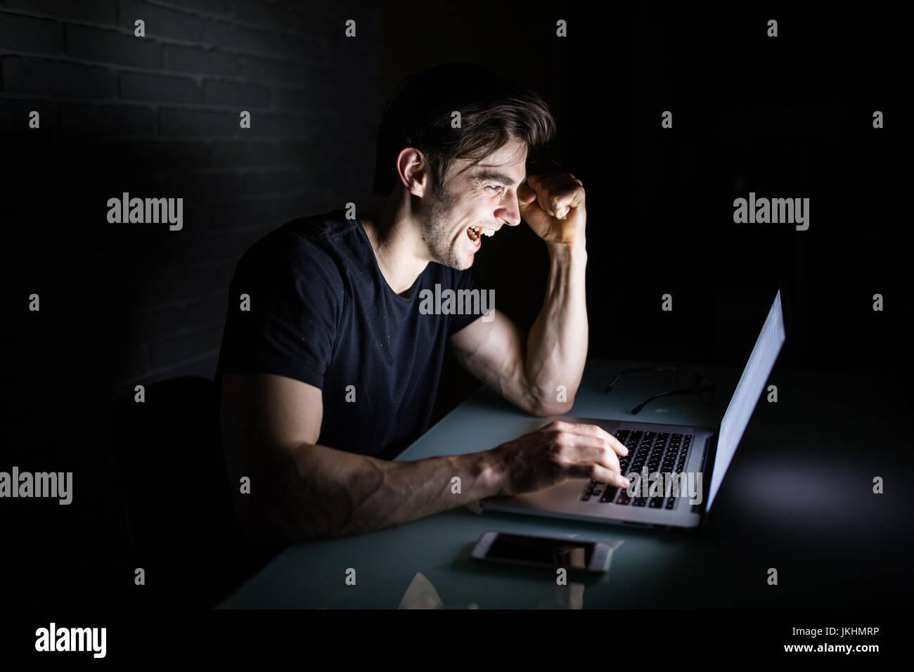 Joven trabajando en equipo por la noche en la oscuridad de la oficina el diseñador trabaja en la tarde. Hacker Imagen De Stock