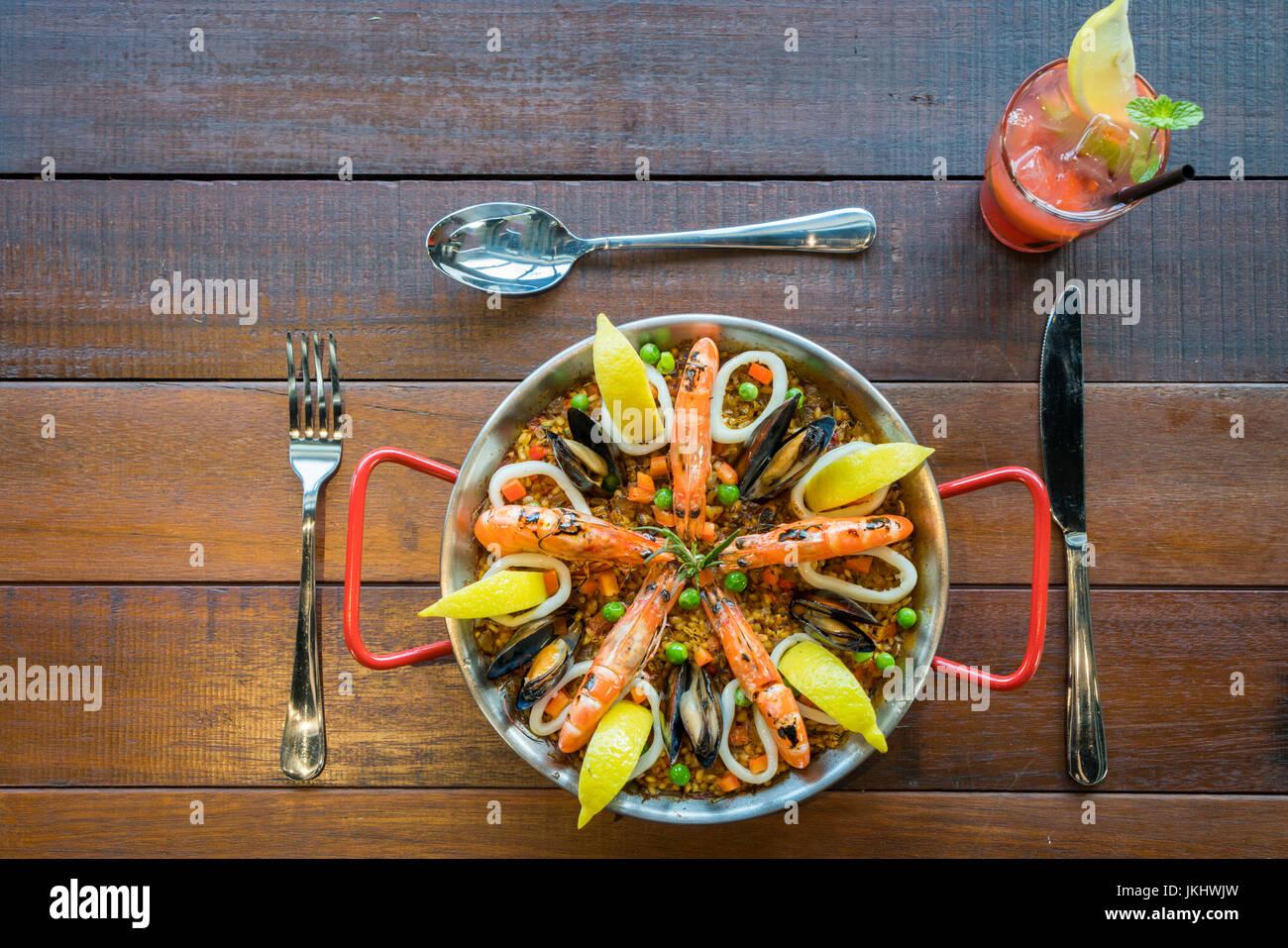 Paella de marisco con verduras y azafrán servido en el tradicional pan vista desde arriba. Foto de stock