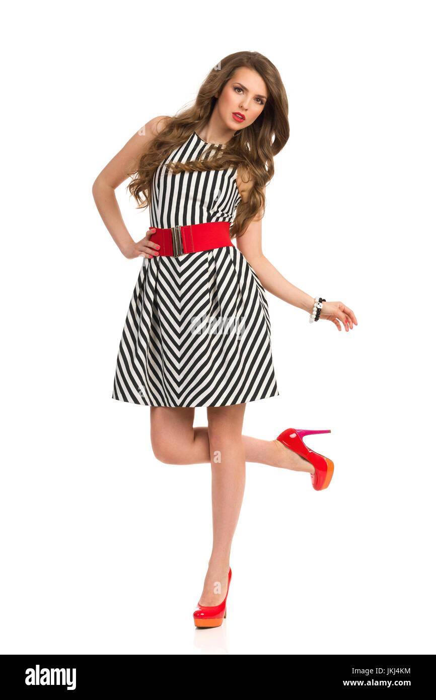 7dbfc8e5ed Hermosa mujer elegante en blanco y negro vestido de rayas y los zapatos de  tacón alto de pie sobre una pierna