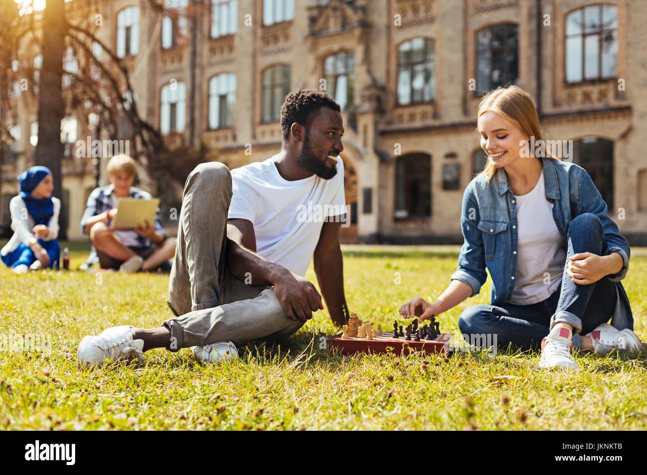 Maravillosos amigos brillantes jugando ajedrez Foto de stock