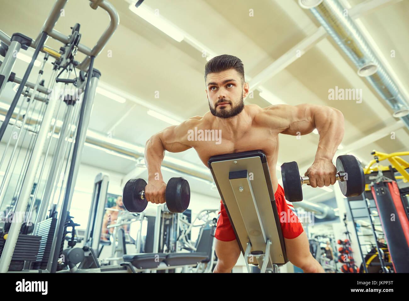 No culturista ejercicios con pesas en el gimnasio. Imagen De Stock