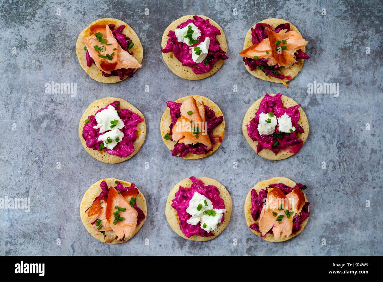 Blinis con remolacha, rábano picante, salmón ahumado en caliente y cabra chhese Foto de stock