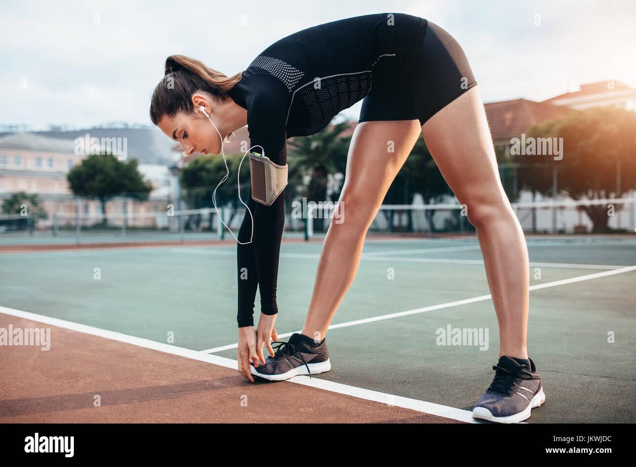 Hermosa muchacha haciendo ejercicios de estiramiento en el exterior. Sportswoman haciendo ejercicio de calentamiento Imagen De Stock