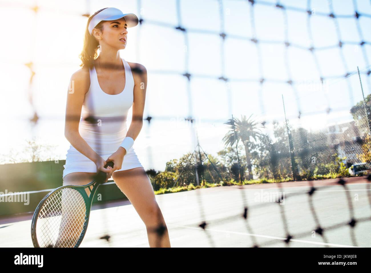 Retrato de una hermosa joven jugador de tenis con la raqueta en la cancha. Sportswoman jugando un partido de tenis. Imagen De Stock