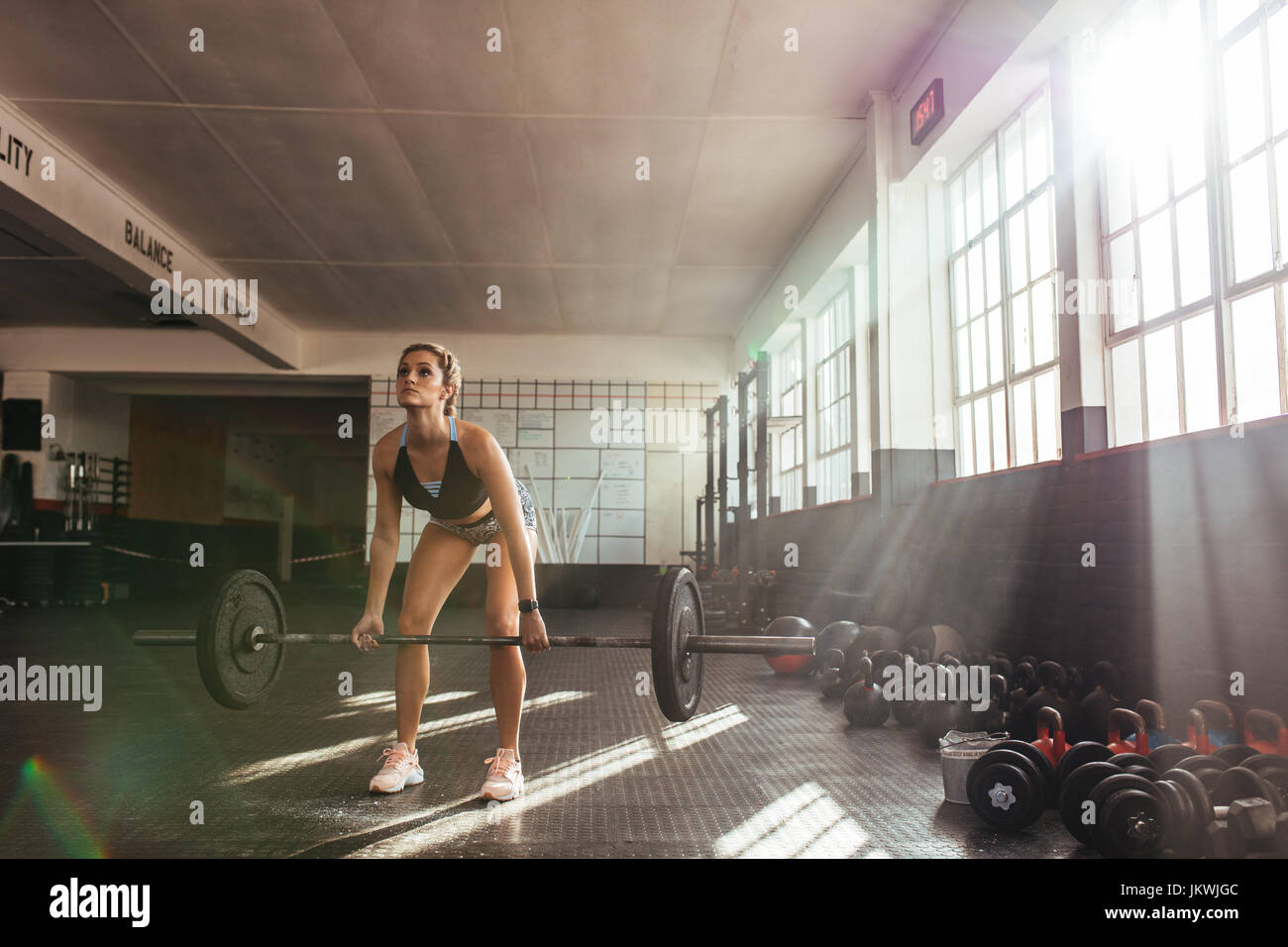 Mujer fuerte de levantamiento de pesas en el gimnasio para el entrenamiento de los músculos. Atleta ejercicio Imagen De Stock