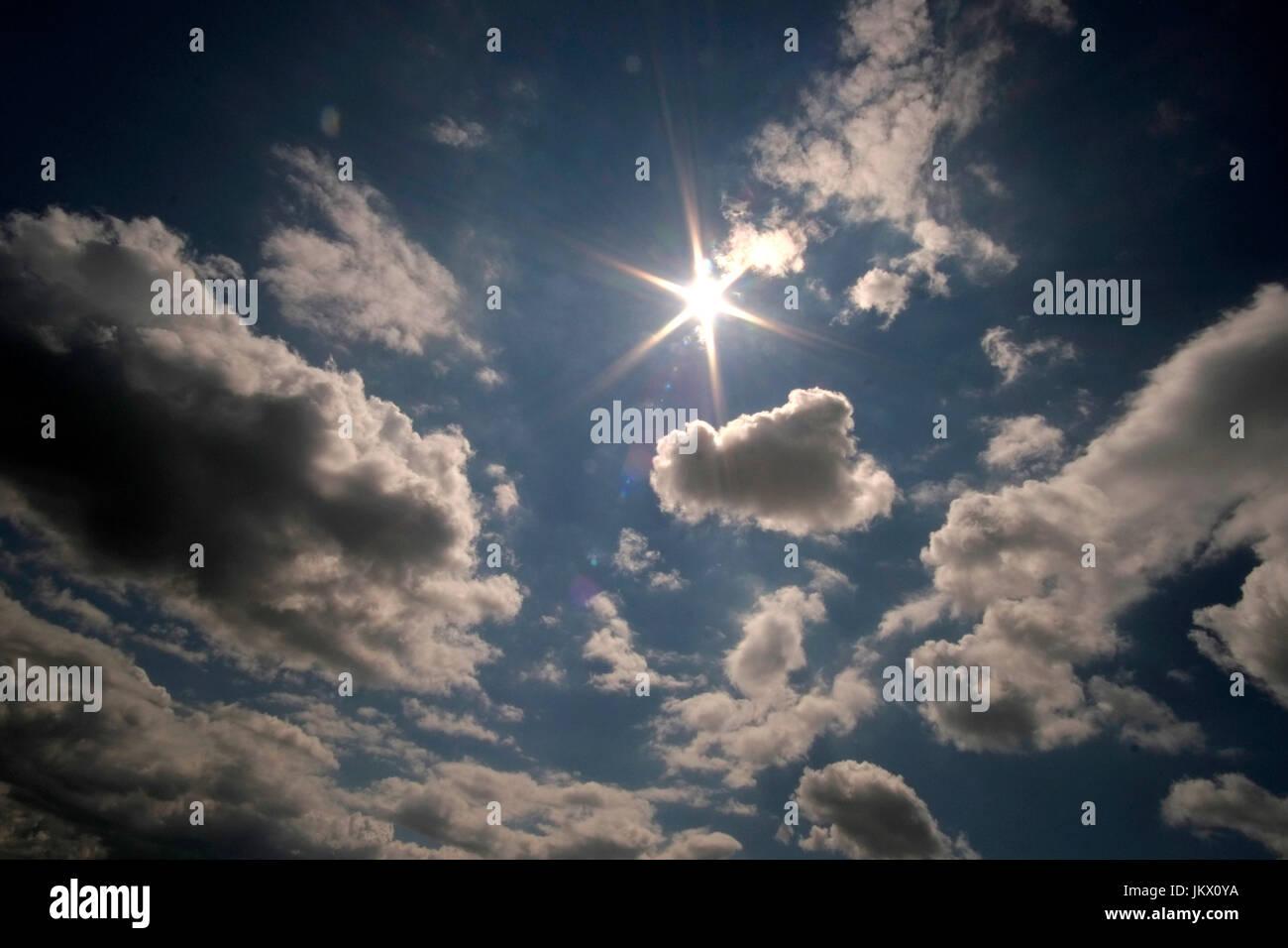 Un cielo azul con nubes blancas y un sol destello. Foto de stock