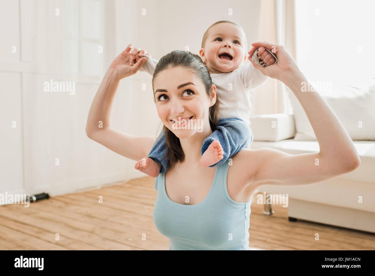 Retrato de una joven madre que llevaba a su hijo en casa piggyback Imagen De Stock