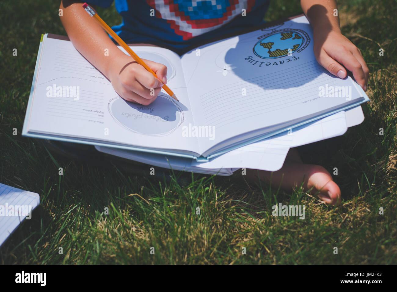 Un joven escribe en un cuaderno de aprendizaje para la educación escolar de vuelta a la escuela. Imagen De Stock