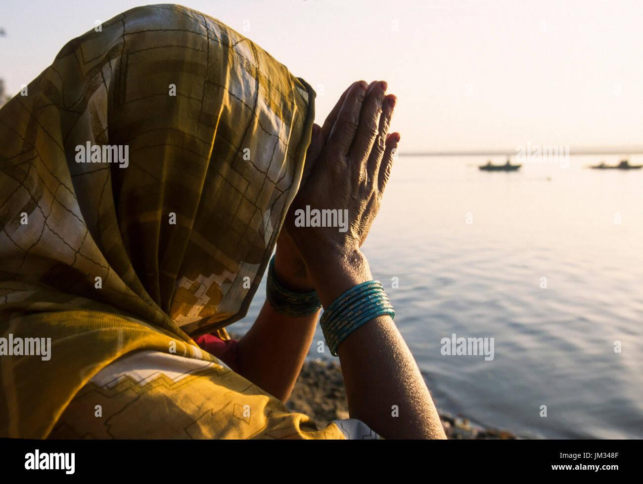 La India, Uttar Pradesh, Varanasi, la mujer hindú de mano plegable para la oración de la mañana del Señor Shiva y de la diosa ganga en el río Ganges, mirando el amanecer, el viejo Banaras o Kashi o ANANDAVANA ( bosque de Bliss ) es un lugar sagrado para los hindúes para alcanzar Moksha significado la salvación del eterno círculo de renacimiento, el Ganges río es un lugar de paso de la tierra al cielo, un lugar muy religioso para la iluminación bliss devoción purificación Imagen De Stock
