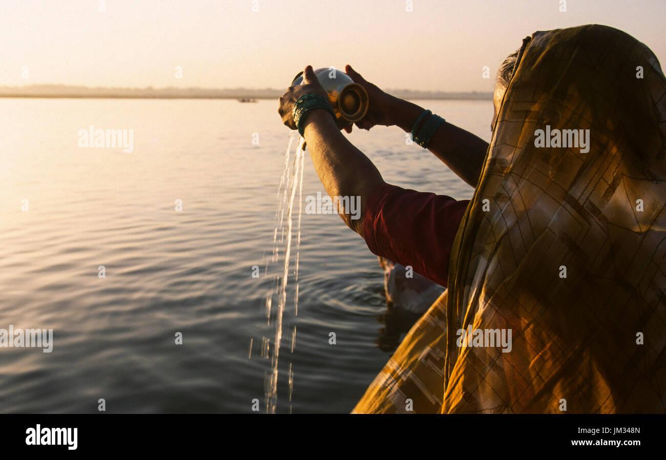La India, Uttar Pradesh, Varanasi, la mujer hindú en la oración de la mañana del Señor Shiva y de la diosa Ganga Ganga santo agua vertido en el río Ganges, el viejo Banaras o Kashi o ANANDAVANA ( bosque de Bliss ) es un lugar sagrado para los hindúes para alcanzar Moksha significado la salvación del eterno círculo de renacimiento, el Ganges río es un lugar de paso de la tierra al cielo, un lugar muy religioso para la iluminación bliss devoción purificación Imagen De Stock