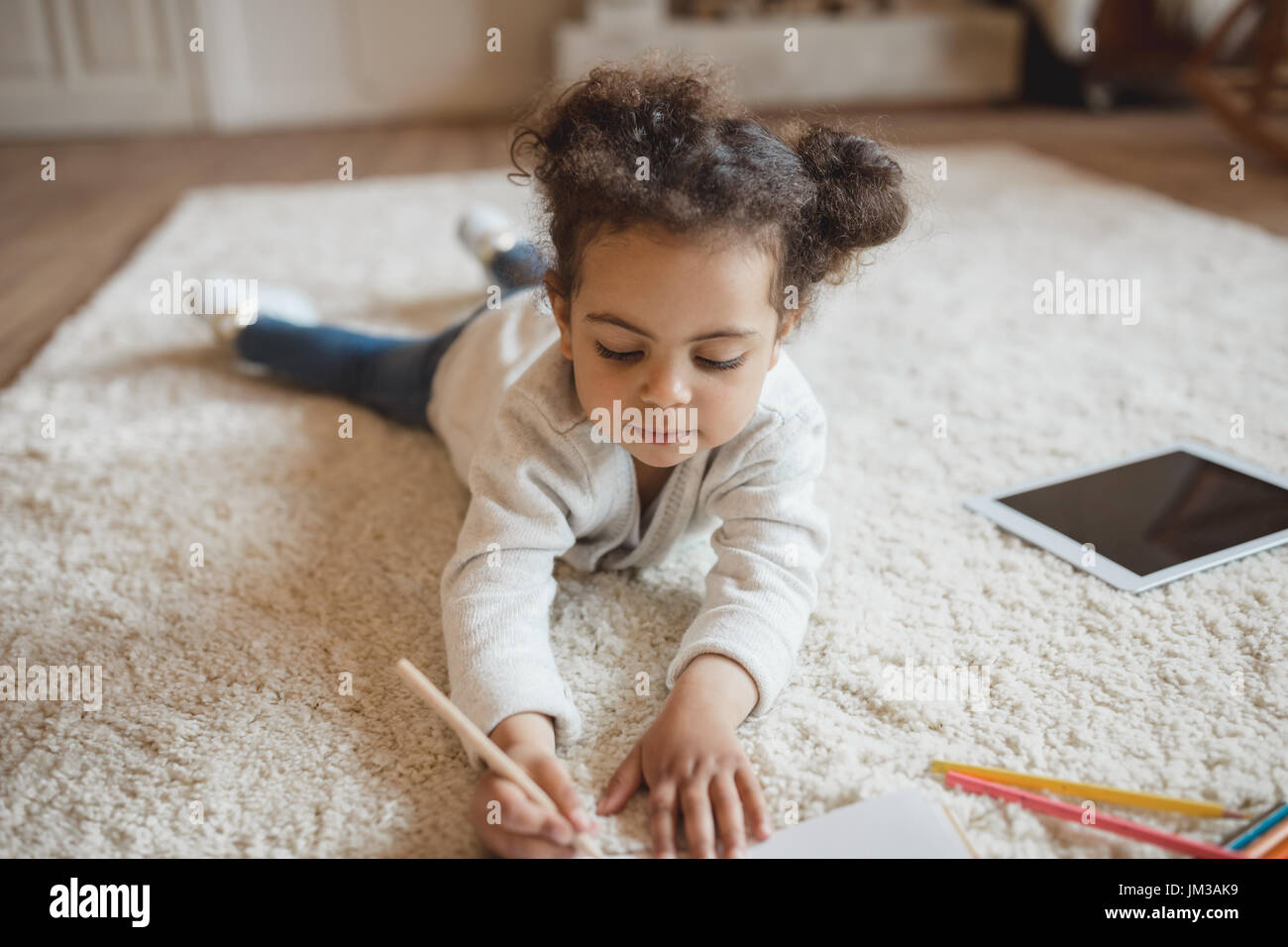 Adorable pequeño African American Girl de dibujo con lápices y acostado sobre una alfombra en casa Imagen De Stock
