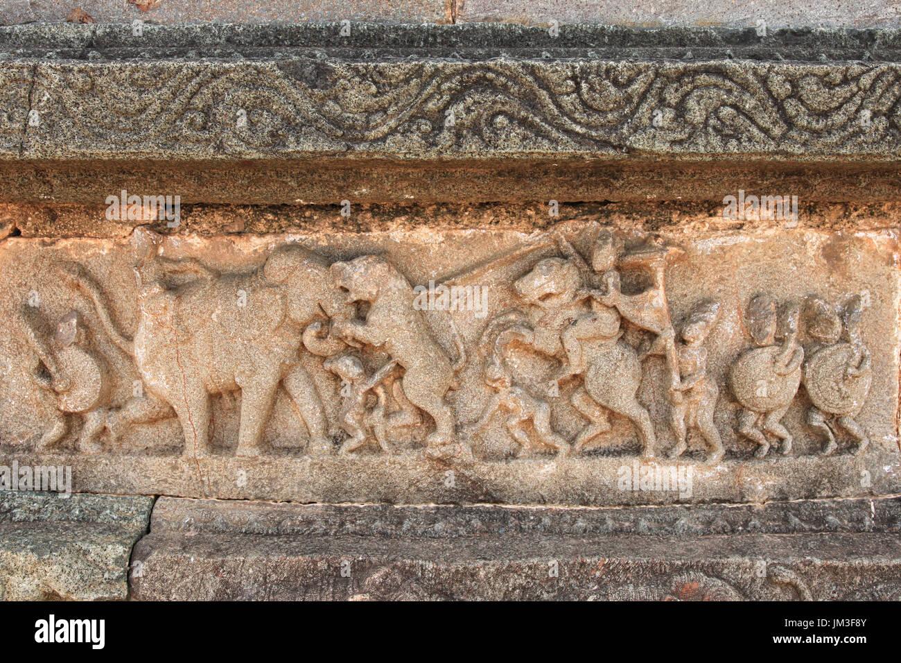 Cazar un tigre por el Rey a caballo en esculturas en el muro del templo, Hampi, India Imagen De Stock
