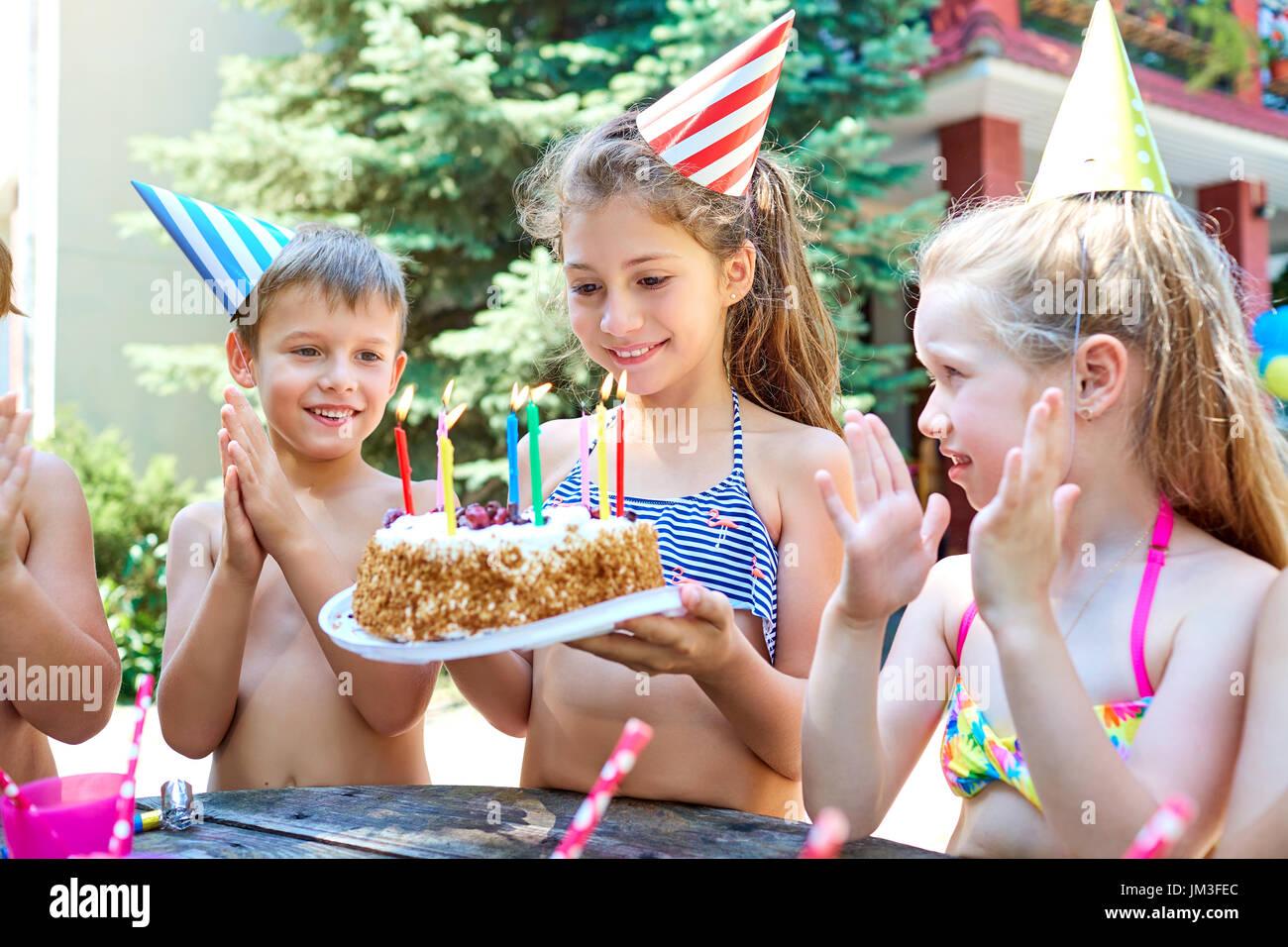 Cumpleaños con niños en sombreros en el verano. Imagen De Stock