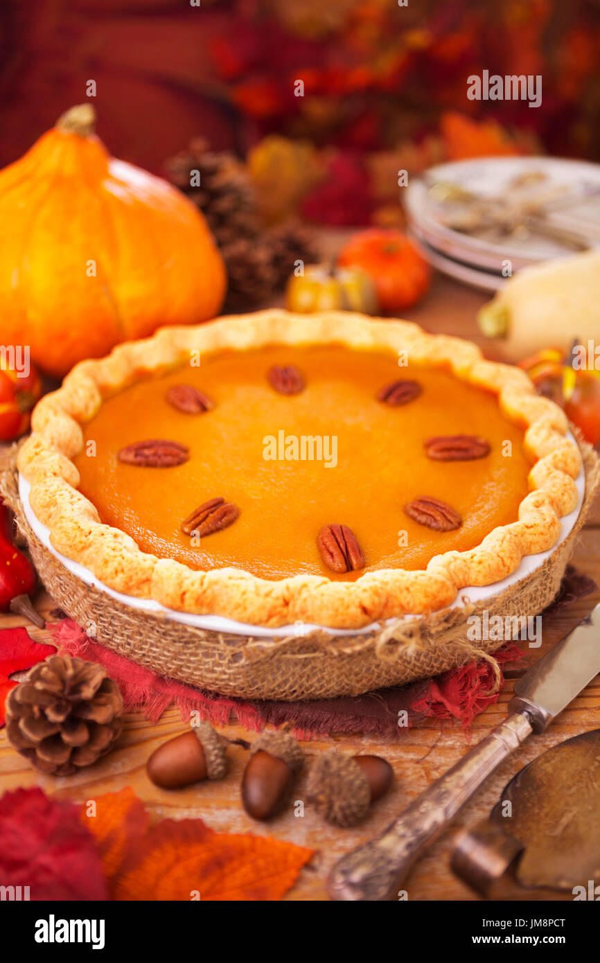 Pastel de calabaza casero sobre una mesa rústica con decoraciones de otoño. Foto de stock