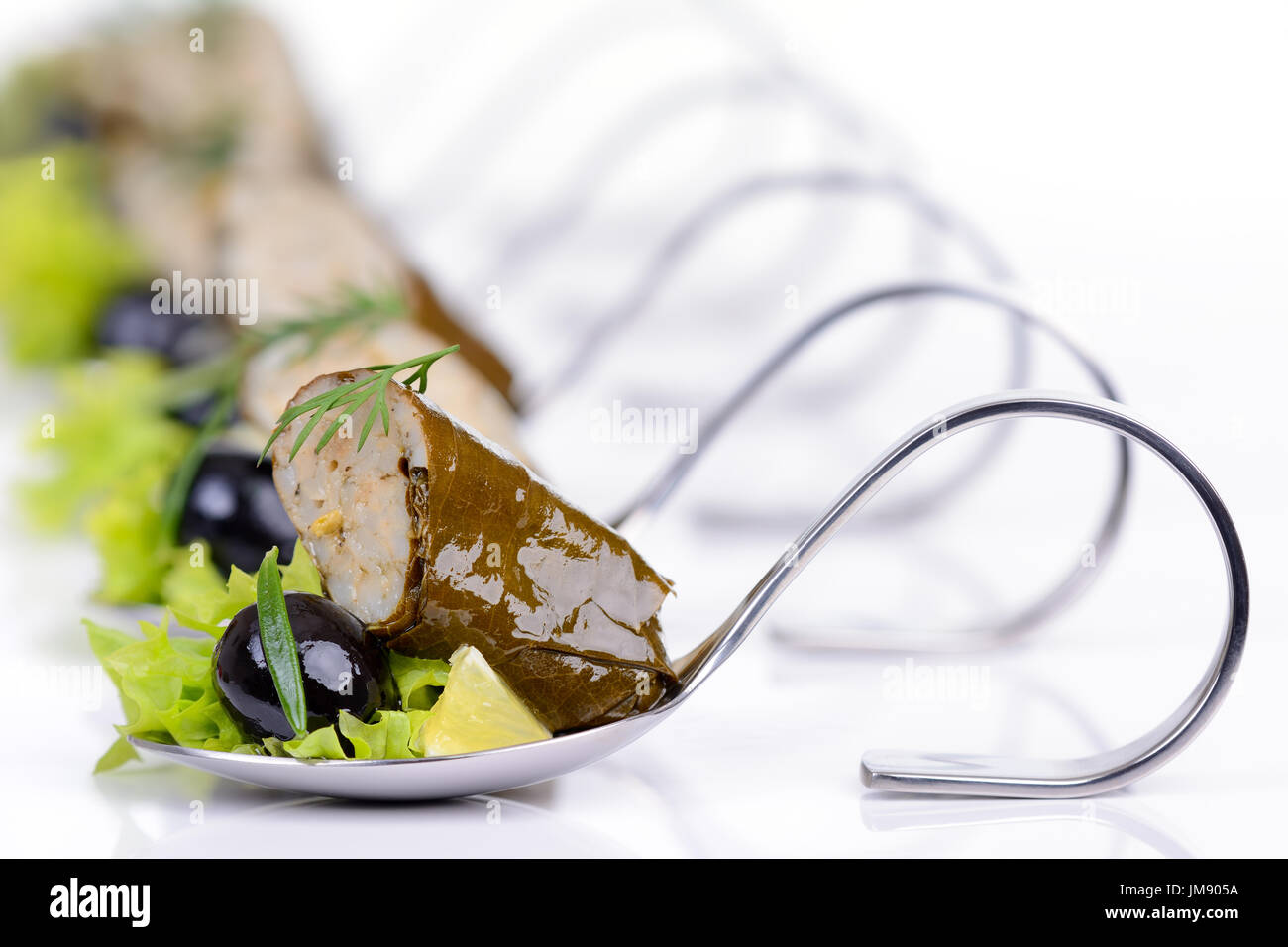 Hojas de uva rellenas con aceitunas negras en cucharas de aperitivo Foto de stock