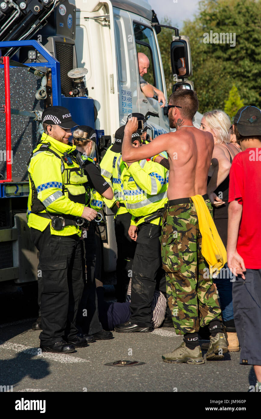 Enfrentamiento verbal con supuestas agresivo policía. Manifestantes anti-fracking detener el convoy de camiones entregando a cuadrillas sitio exploratoria Imagen De Stock