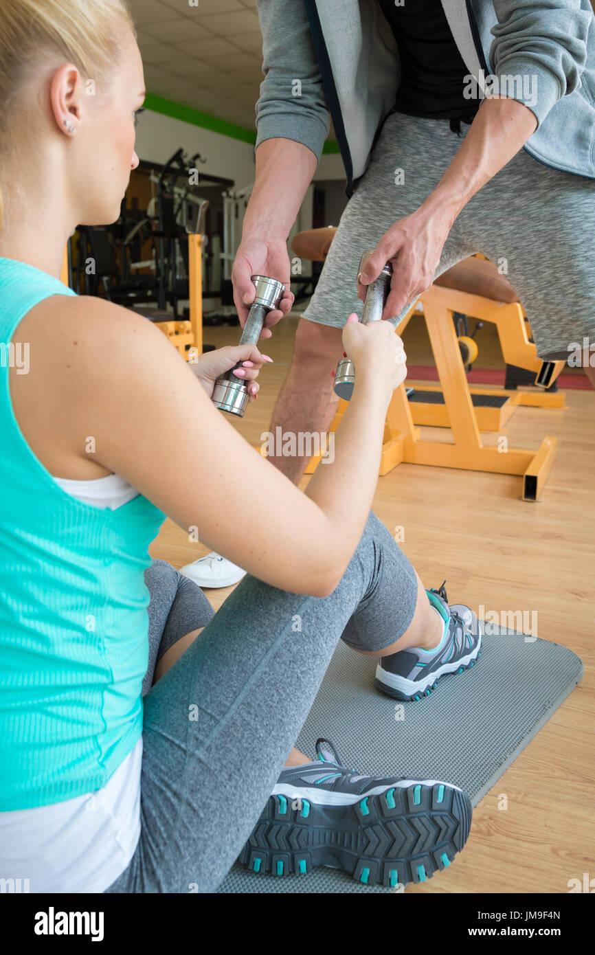 Entrega personal trainer pesas para mujer joven durante la sesión de ejercicio físico Imagen De Stock
