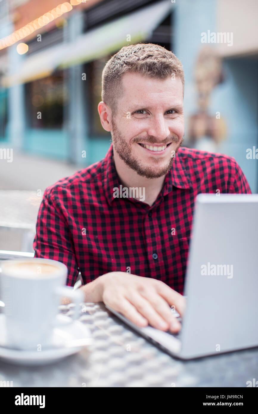 Retrato de joven en la cafetería al aire libre trabajando en el portátil Imagen De Stock