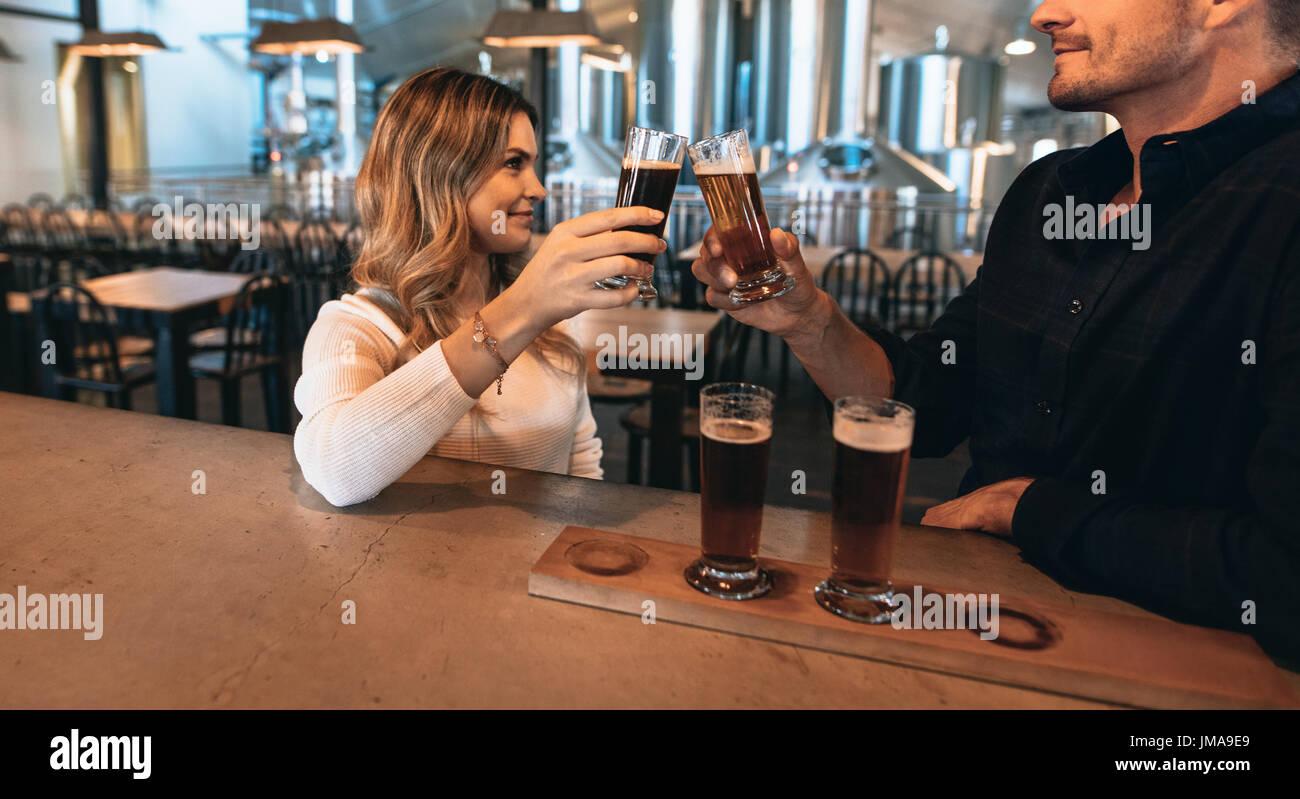 Pareja en el bar con diferentes variedades de cervezas artesanales. Están en la cervecería y tostar los vasos de cerveza. Imagen De Stock
