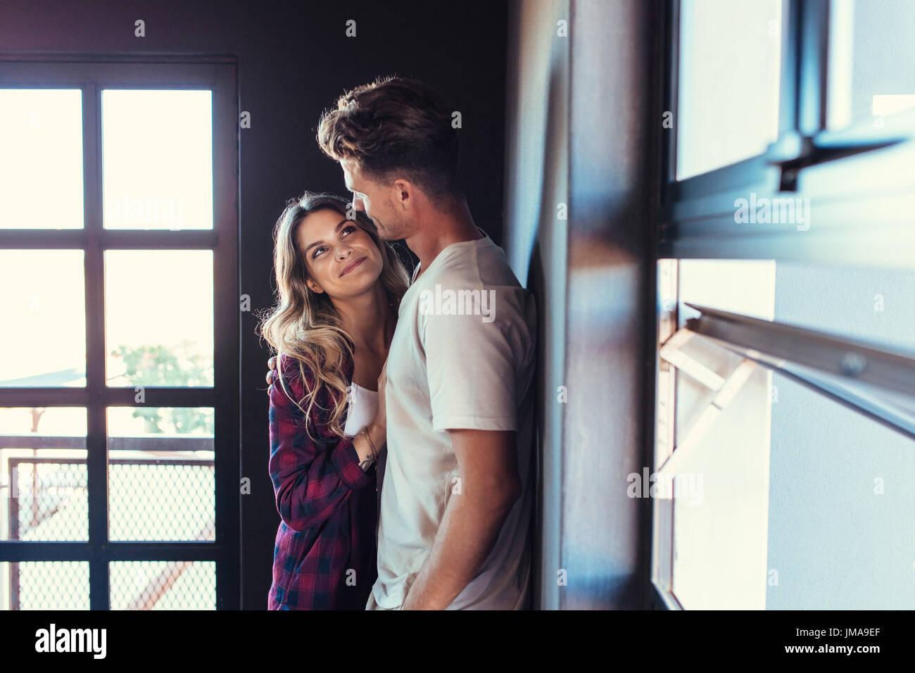 Retrato de la romántica pareja joven mirando el uno al otro. El hombre y la mujer en el amor parados juntos en interiores. Imagen De Stock